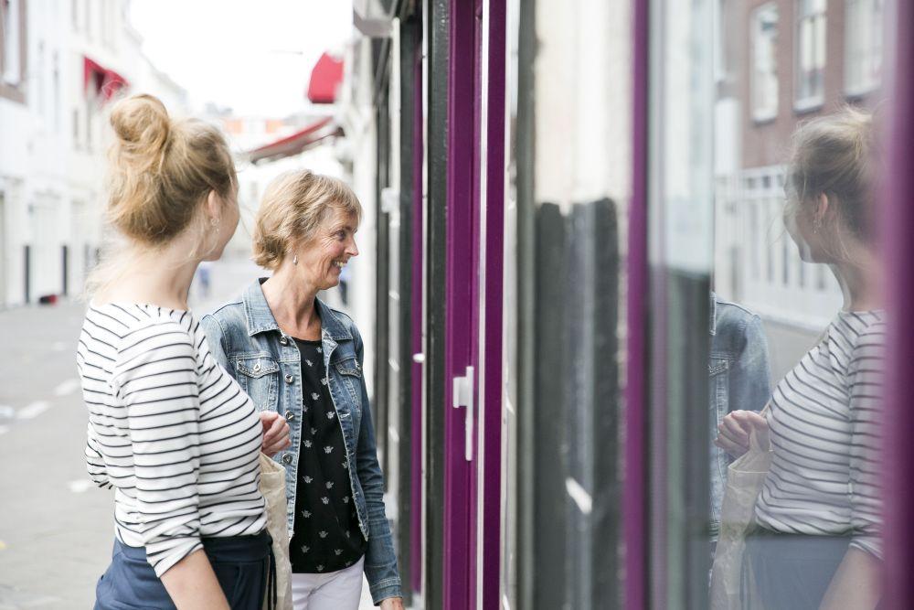 Vrijwilligsters van de Haven maken contact met een vrouw achter het raam. (beeld Havenkerk)